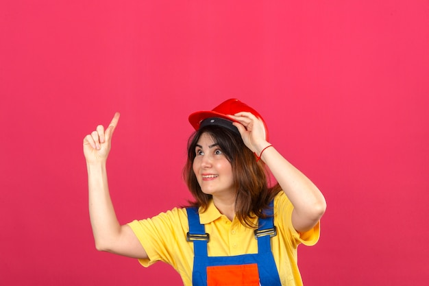 Erbauerfrau, die bauuniform und sicherheitshelm trägt, der beiseite zeigt finger zeigt, der große neue idee über isolierter rosa wand hat