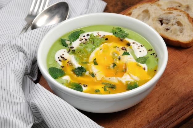 Erbsenpüree-suppe mit pochiertem ei, sauerrahm, minzblättern, gewürzt.