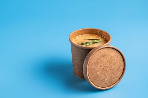 Erbsensuppe in einwegbechern aus papier zum mitnehmen oder zur lieferung von lebensmitteln auf blauem hintergrund