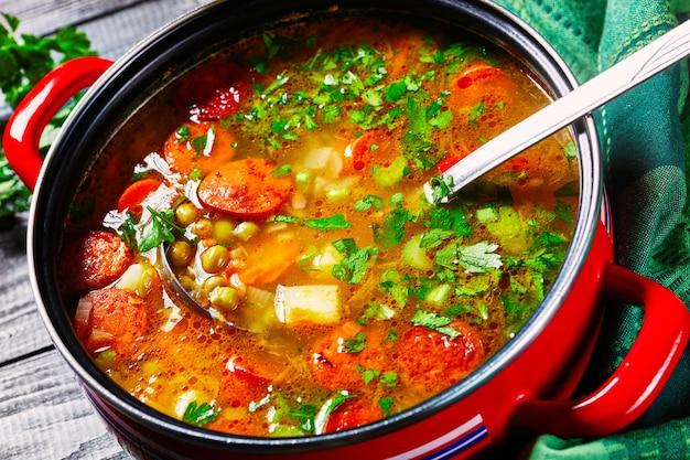 Erbsensuppe mit bayerischer wurst, pastinaken, karotten mit petersilie und frühlingszwiebeln, serviert auf einem roten antihaftbeschichteten topf mit einer suppenkelle auf dunkler holzoberfläche, draufsicht, nahaufnahme