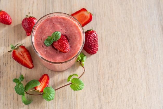 Erdbeer-bananen-smoothies in gläsern mit zutaten auf hellem holztisch. draufsicht