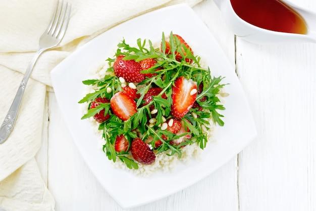 Erdbeer-, couscous-, zedern- und rucola-salat mit balsamico-essig und olivenöl auf einem teller