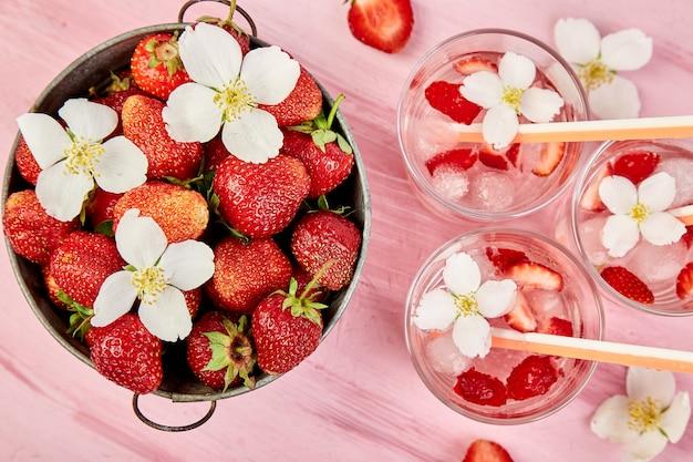 Erdbeer-detox-wasser mit jasminblüte. sommergetränk oder tee.