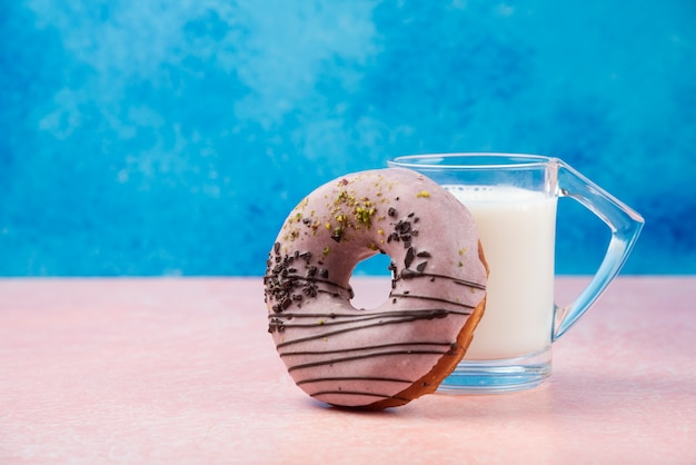 Erdbeer donut mit dekorationen und einem glas milch auf rosa tisch.