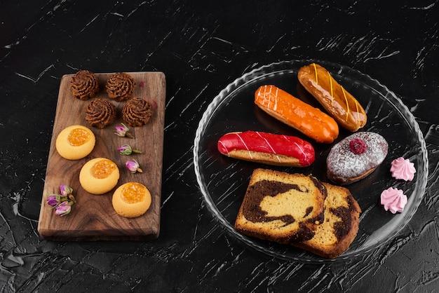Erdbeer-eclair mit schokoladenmuffin und kuchenstücken.