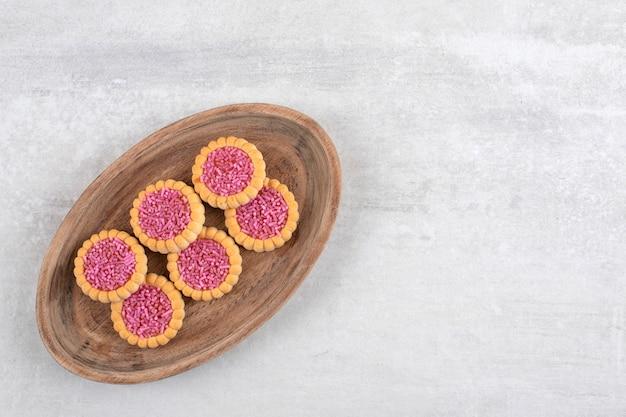 Erdbeer-gelee-kekse auf einem brett, auf dem marmor.