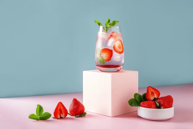 Erdbeer-mojito auf blauem hintergrund und rosafarbenem podium. erfrischendes sommergetränk mit kopienraum