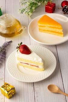 Erdbeer-sahne-kuchen und orangen-fudge-kuchen auf einem weißen teller, dreieckiger kuchen, schöne dekoration mit geschenkboxen und blumen