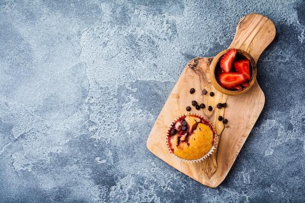 Erdbeer-schokoladen-cupcakes-muffins auf altem holzständer auf betongrauer oberfläche