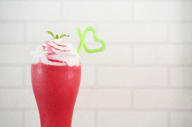 Erdbeer-smoothie auf weißem ziegel-hintergrund.