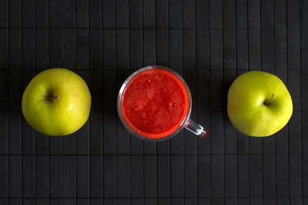 Erdbeer-smoothie in einer glasschale und zwei grünen äpfeln