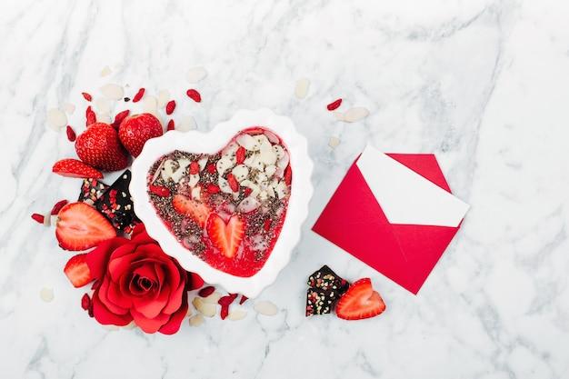 Erdbeer-smoothie in einer schüssel in form eines herzens und einer valentinskarte