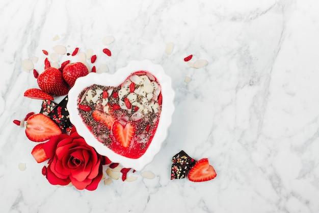 Erdbeer-smoothie in einer schüssel in herzform mit kopierraum