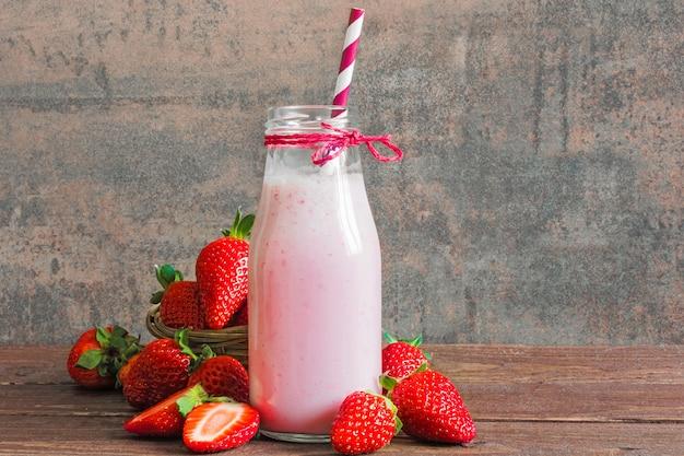 Erdbeer-smoothie oder milchshake in einer flasche mit strohhalm