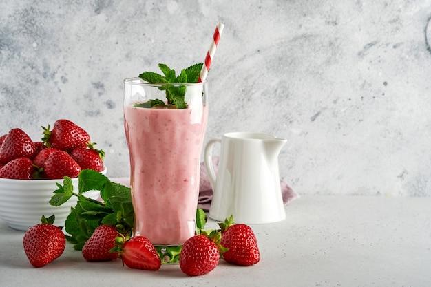 Erdbeer-smoothie oder milchshake mit beeren und minze im hohen glas auf hellgrauem hintergrund. sommergetränkshake, milchshake und erfrischungs-bio-konzept. platz für text.