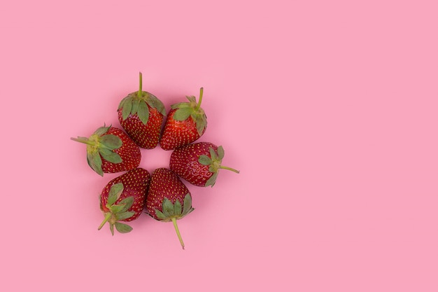 Erdbeer-teamwork auf rosa hintergrund