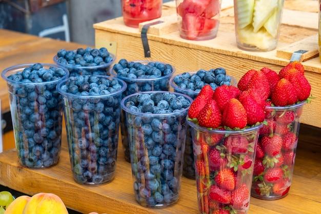 Erdbeer- und blaubeerbeeren auf einem markt im freien. frische reife früchte