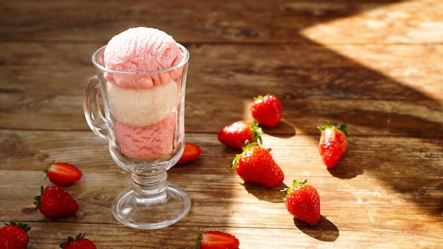 Erdbeer- und vanilleeis in einem glasglas. erdbeeren auf holzuntergrund