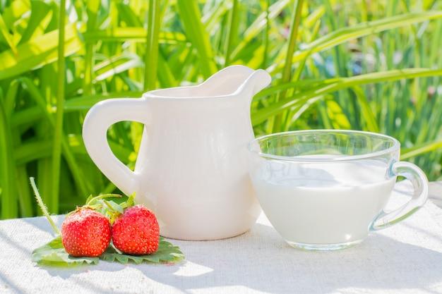 Erdbeerbeeren und blätter, ein krug und eine schale mit milch auf einer serviette auf einem hintergrund des grases