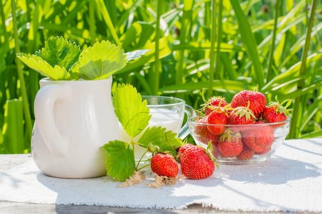 Erdbeerbeeren und -blätter, eine schüssel erdbeeren, ein krug und eine schale milch auf einer serviette auf einem holztisch