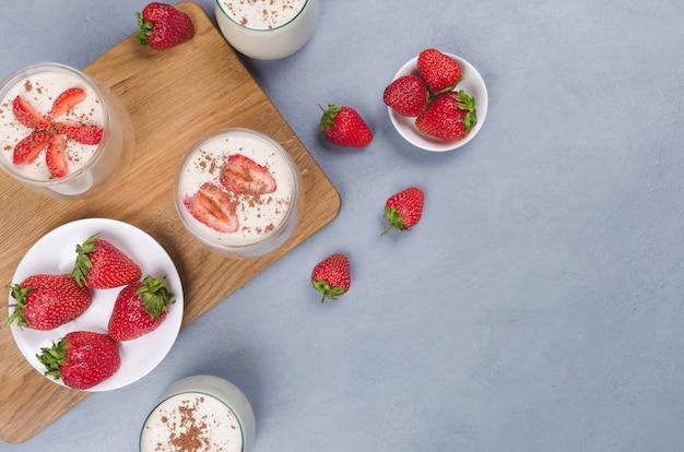 Erdbeerdessert in einem glas mit erdbeeren auf einem grauen tisch mit leinenserviette