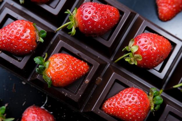Erdbeerdessert in schokolade vor dunklem hintergrund