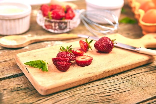 Erdbeere auf schneidebrett. rohstoffe zum kochen erdbeertorte