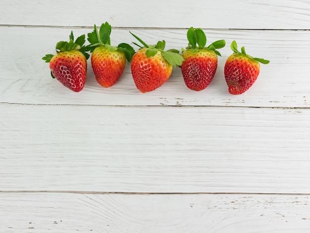 Erdbeere auf weißem holztischhintergrund