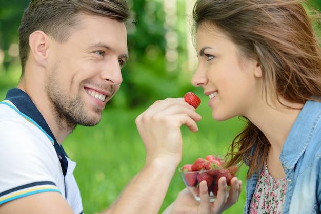 Erdbeere für sie. junge männer füttern seine freundin