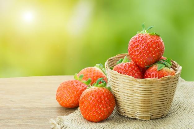 Erdbeere im bambuskorb auf sack auf holztisch mit grünem naturhintergrund