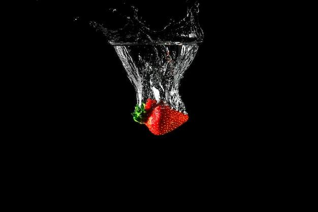 Erdbeere im wasser mit schwarzem hintergrund