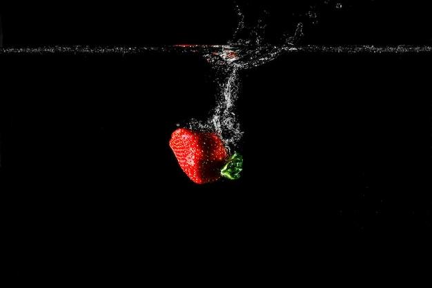 Erdbeere im wasser mit schwarzem hintergrund.