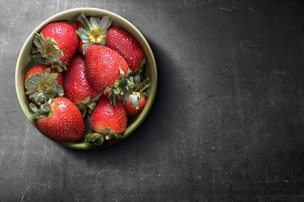 Erdbeere in der schüssel auf einem schwarzen