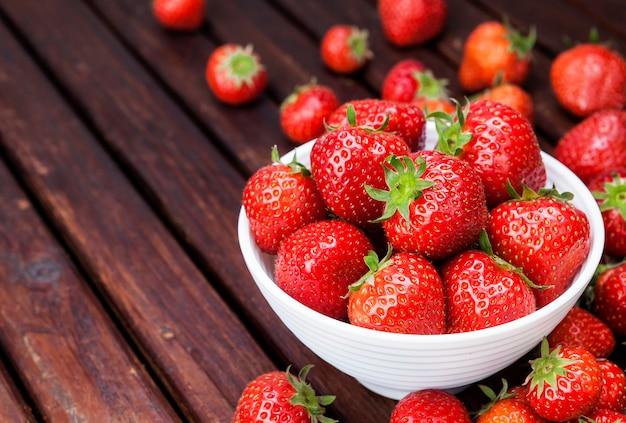 Erdbeere in der schüssel auf holztisch