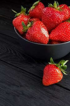 Erdbeere in der schwarzen schüssel auf der schwarzen holzoberfläche. nahansicht.