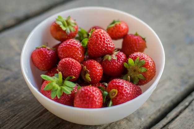 Erdbeere in einer platte auf einem hölzernen hintergrund