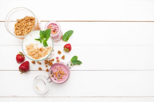 Erdbeere mit joghurt auf weißem rustikalem holz