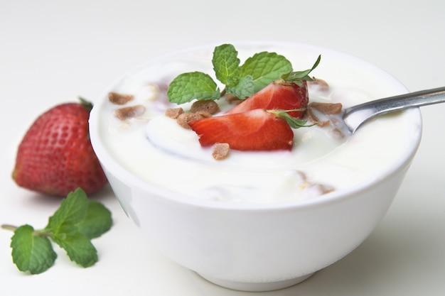 Erdbeere mit joghurt und minze in der schüssel auf hölzernem hintergrund