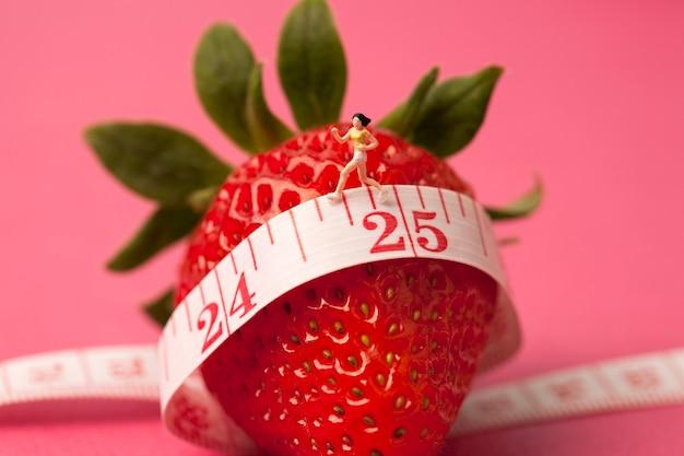 Erdbeere mit maßband auf rosa hintergrund