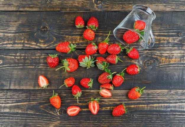 Erdbeere mit tasse auf holzoberfläche