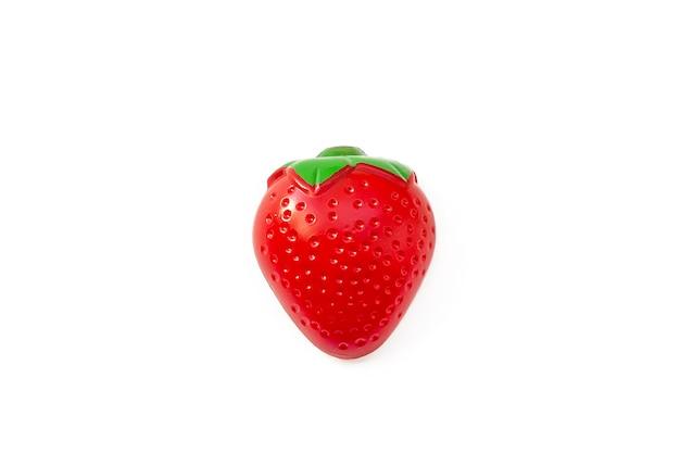 Erdbeere. spielzeugplastikfrucht lokalisiert auf weißem hintergrund. plastikfrucht für das spiel. spielen im kinderladen.