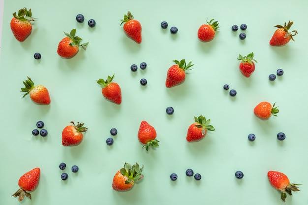 Erdbeere und blaubeere auf pastellgrünem hintergrund. flache lage, draufsicht auf das essen