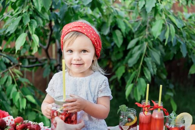 Erdbeere und minze gossen detoxwasser hinein. erdbeerlimonade mit eis und minze als sommerliches erfrischungsgetränk in gläsern. kalte erfrischungsgetränke mit obst.