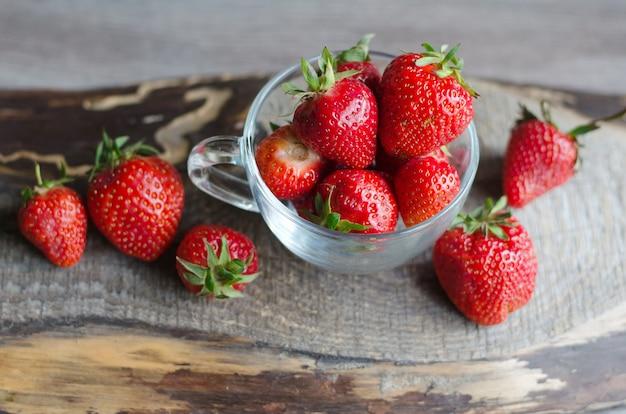Erdbeere und würfel des eises in einem glas auf hölzernem hintergrund