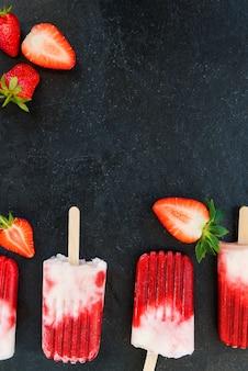 Erdbeereis am stiel mit erdbeersaft auf schwarzem hintergrund