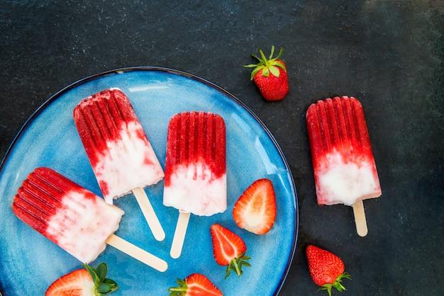 Erdbeereis am stiel mit erdbeersaft