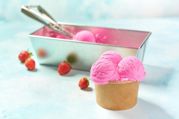 Erdbeereis und frische erdbeere im pappbecher auf minzfarbenhintergrund