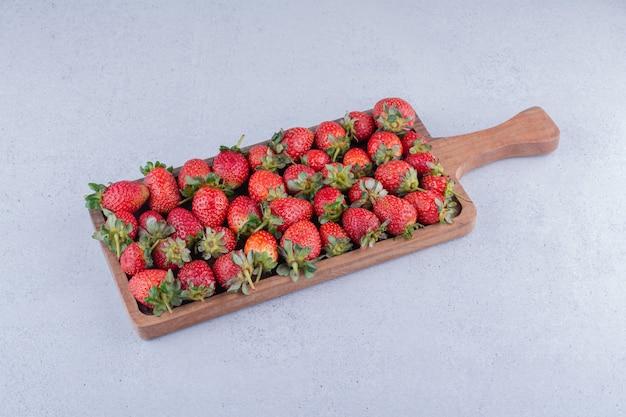 Erdbeeren angeordnet auf einem holzbrett auf marmorhintergrund.