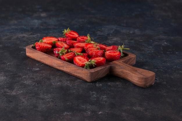 Erdbeeren auf einem holzbrett auf dem grauen marmor