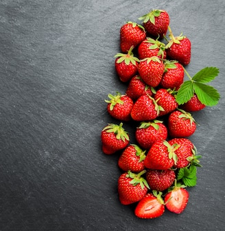Erdbeeren auf einem schwarzen steinhintergrund